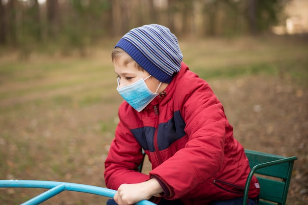Small child playing on the playground in park during coronavirus epidemic. young boy wearing medical mask for protection from virus Premium Photo