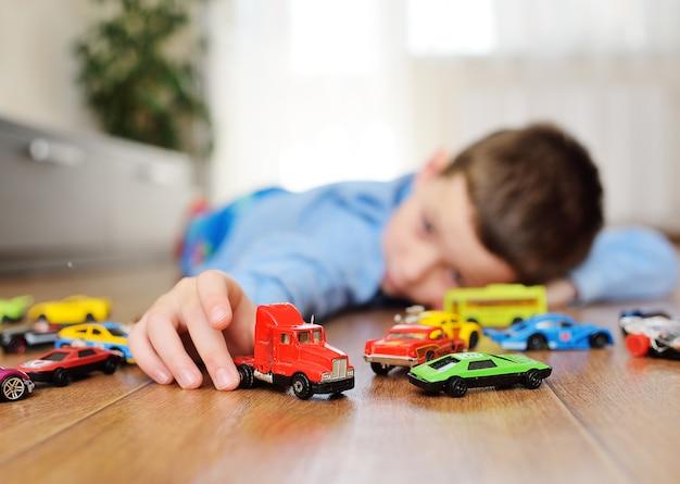 おもちゃの車を遊んでいる小さな子供幼児男の子 Premium写真