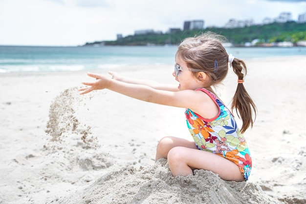 小さな子供が海岸の砂を投げます。夏の娯楽とレクリエーション。 無料写真