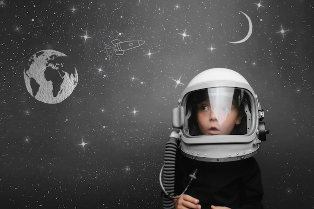 Small child wants to fly an in space wearing an astronaut helmet Premium Photo