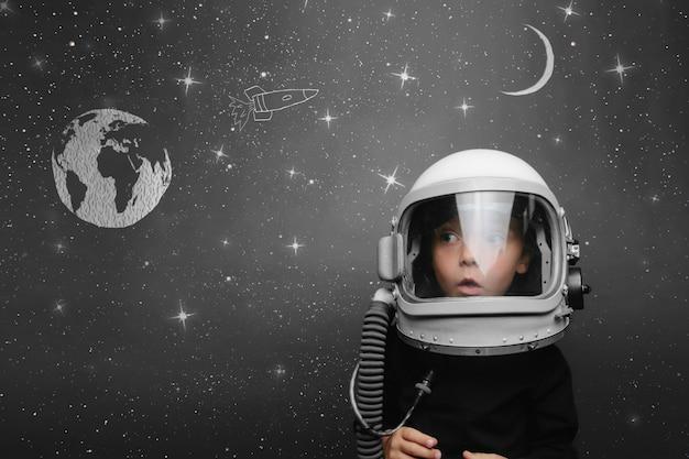 작은 아이가 우주 비행사 헬멧을 쓰고 우주에서 날고 싶어 프리미엄 사진