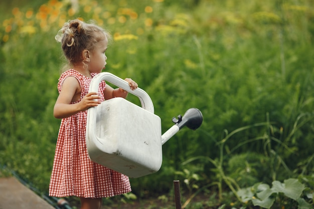 花の水まき缶を持つ小さな子供を注ぐ。じょうごを持つ少女。ピンクのドレスの子。 無料写真