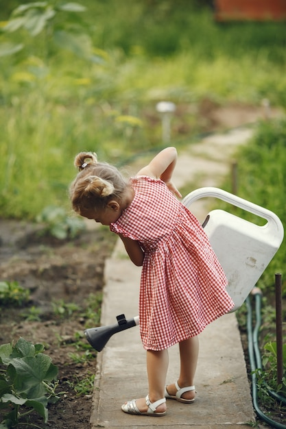 Small child with a watering can with flowers pour. girl with a funnel. child in a pink dress. Free Photo