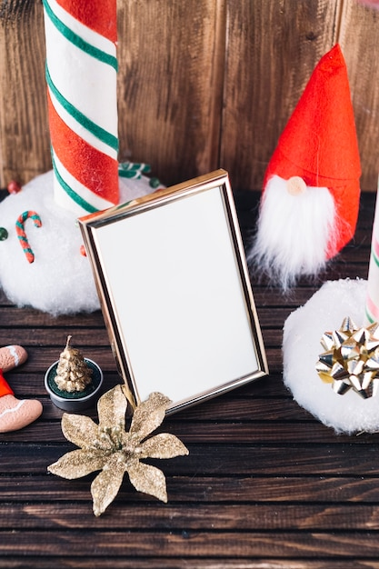 Small christmas elf with blank frame on table Free Photo
