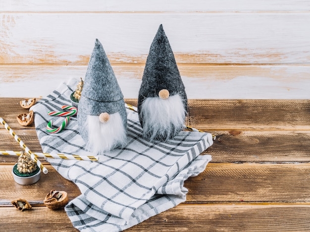 Small christmas elves with candy canes on table Free Photo