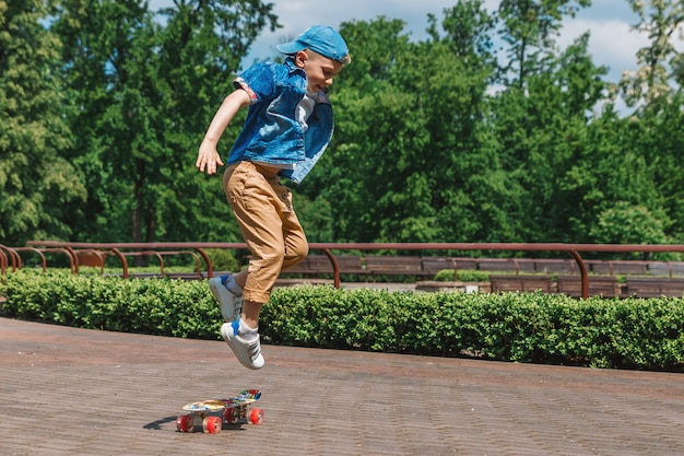 A small city boy and a skateboard. a young guy is riding in a park on a skateboard Premium Photo
