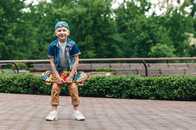 A small city boy and a skateboard. a young guy is standing in the park and holding a skateboard Premium Photo