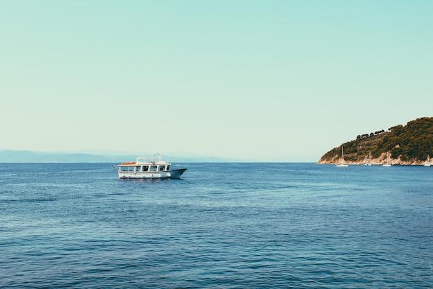 Небольшие круизные лайнеры у моря недалеко от греческих островов. предпосылка спокойного моря и голубого неба. ландшафт оранжевой горы с зелеными деревьями на нервюрах. Premium Фотографии