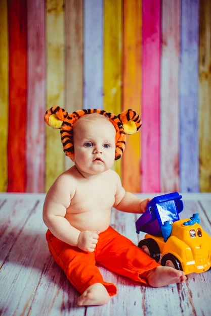 small cute smiling baby boy in tiger suit sitting on the floor photo