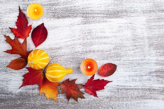 素朴な木製のテーブルに小さな装飾的なカボチャと落ち葉の花輪 Premium写真