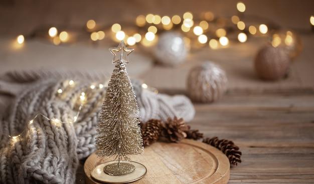 작은 장식 반짝이 크리스마스 트리는 따뜻한 색상의 Bokeh와 흐릿한 조명의 배경에 닫습니다. 무료 사진