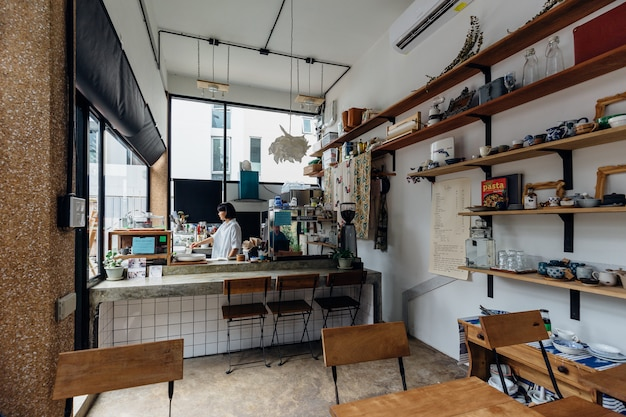 Small dessert cafe. decorated with white color and wooden shelves. Premium Photo