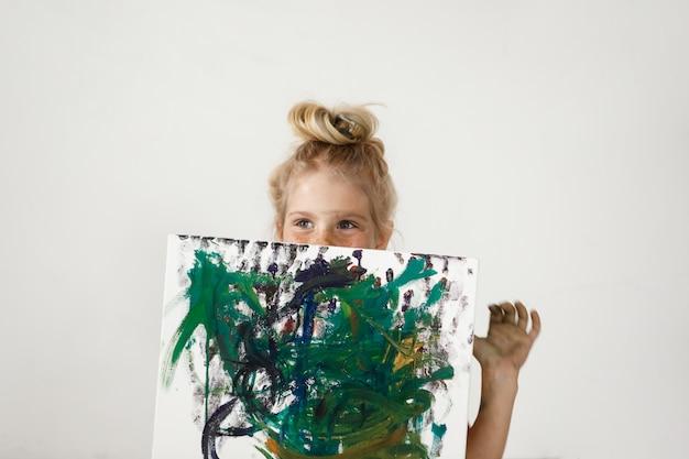 Piccola ragazza bionda europea con gli occhi azzurri e il panino dei capelli che tiene immagine colorata e nasconde il viso. la felicità e la gioia della bambina sono così affascinanti. attività artistiche per bambini. Foto Gratuite