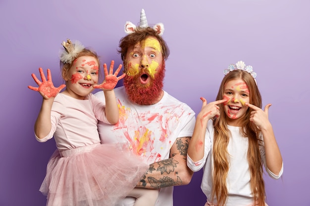 작은 여자 아이는 화려한 구 아슈 그림으로 더러워진 손을 보여주고, 그녀의 기쁜 여동생은 얼굴에 수채화 얼룩이 있고, 아버지는 놀랐고, 어머니가 직장에서 돌아 오기 전에 재미있게 지냅니다. 무료 사진