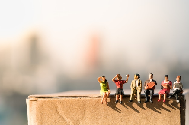 Small figures sitting on paper box with city backgrounds. Premium Photo