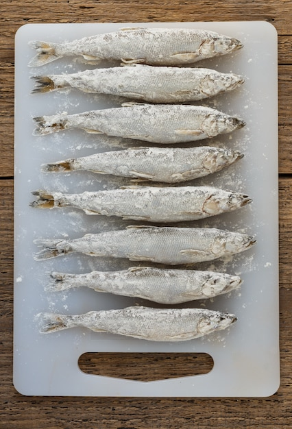 Small fresh fish,  smelt or roach, sprinkled with flour-ready for frying, top view Premium Photo