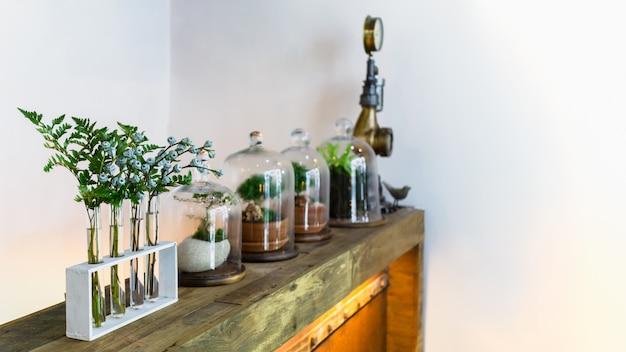 Small garden of terrarium bottle, old wooden shelf and flower in vintage glass bottles Premium Photo