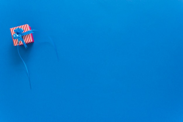 Small gift box on blue background Free Photo