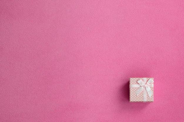 A small gift box in pink with a small bow lies on a blanket of fleece fabric Premium Photo