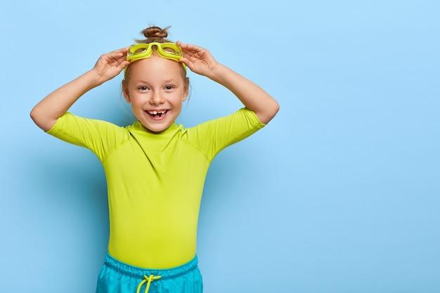 小さな女の子はゴーグルを調整し、プールに浮かぶ準備をします 無料写真