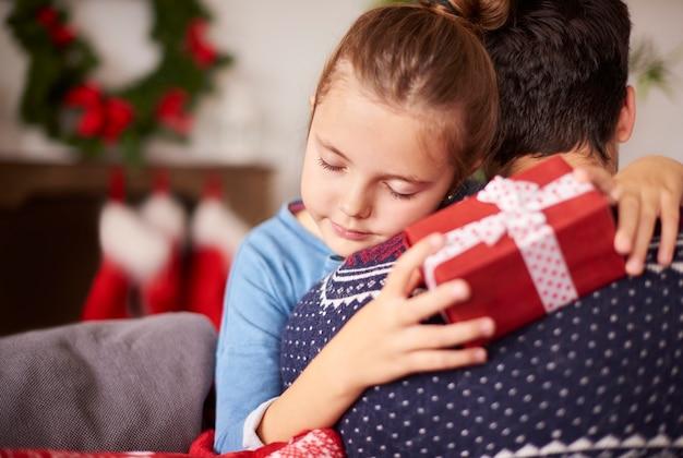 クリスマスに彼女のパパを抱きしめる小さな女の子 無料写真