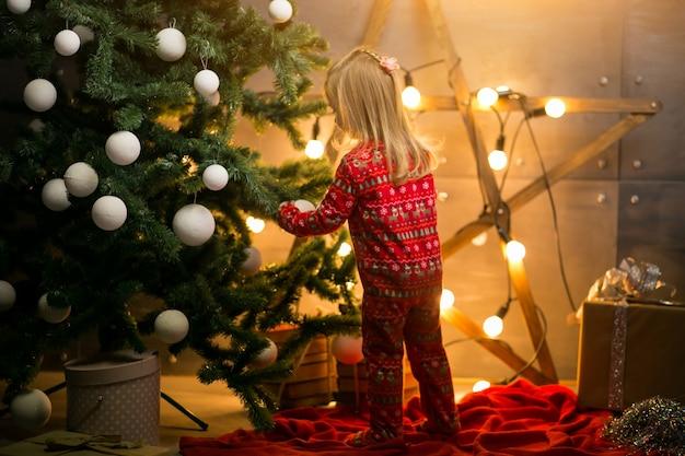 クリスマスツリーのパジャマの小さな女の子 無料写真