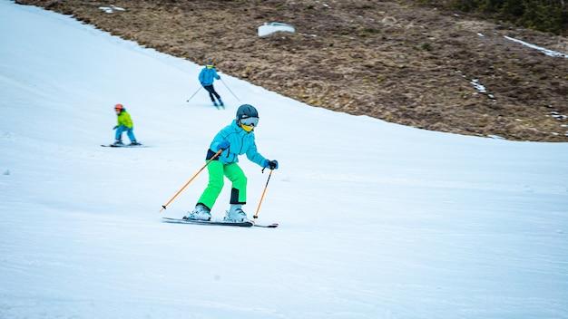 スキーストックでスキーを学ぶ小さな女の子 Premium写真