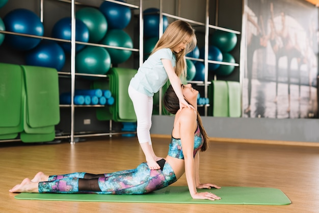 Small girl standing on her mother doing exercise at gym Free Photo