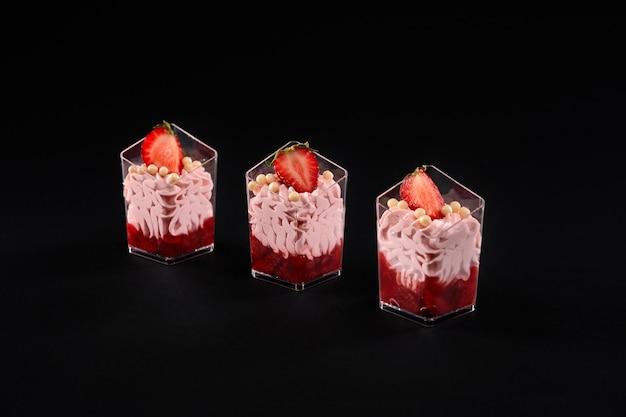 휘핑 핑크 크림과 딸기로 장식 된 레드 잼으로 채워진 작은 잔 프리미엄 사진