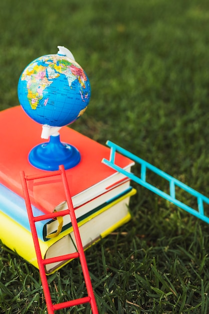 Small globe arranged on top of books stack Free Photo