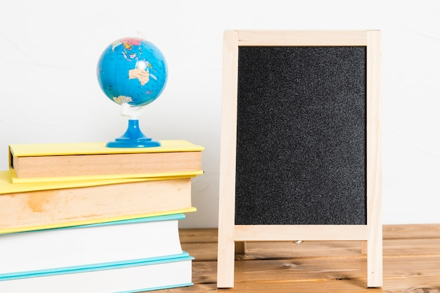 Small globe on books with empty blackboard on wooden table Free Photo