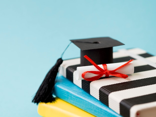 コピースペースと本の山に小さな卒業の帽子 Premium写真