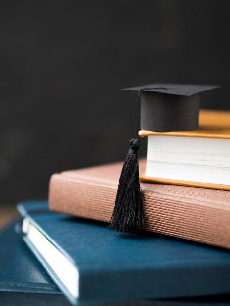 本の山に小さな卒業の帽子 Premium写真