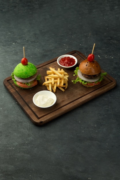 Small green and brown beef burgers served with fries, ketchup and mayonnaise Free Photo