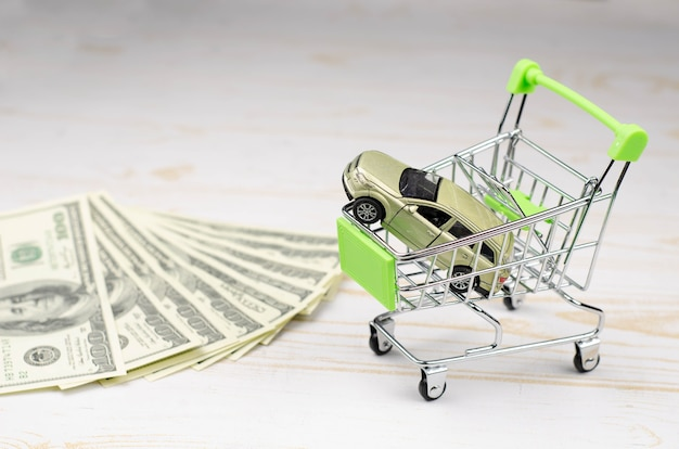 Small green shopping carttrolley with a toy car and 100 dollar banknotes on white wood Premium Photo