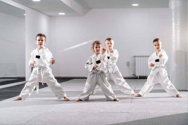 Small group of caucasian kids in doboks practicing taekwondo and warming up for treining while standing barefoot. Premium Photo
