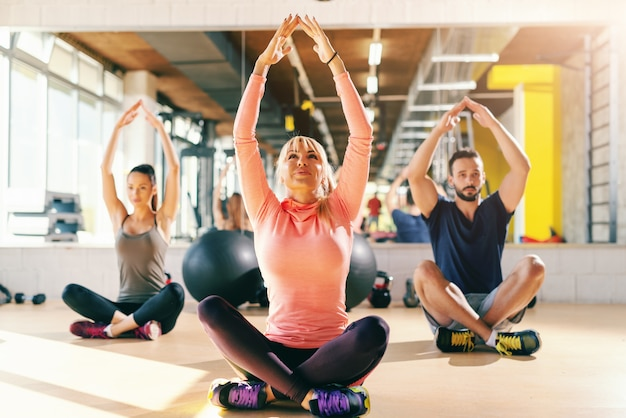 Small group of fit people doing relaxation exercises while sitting on the gym floor with crossed legs. in background mirror. Premium Photo
