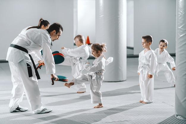 トレーナーのテコンドーと練習しているドックの子供たちの小さなグループは、キックターゲットを蹴りながら動きます。 Premium写真
