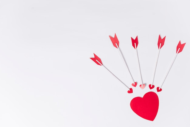 Small heart with love arrows on table Free Photo