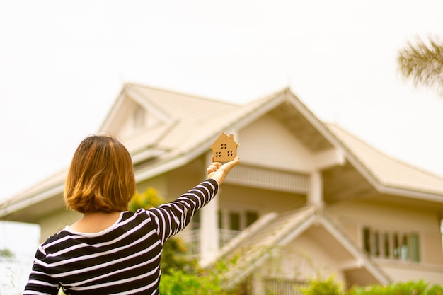 Small home model in woman hand front a home. Premium Photo