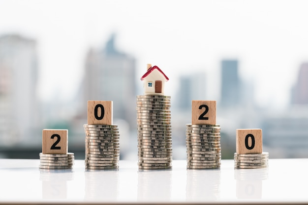 Small house and 2020 wooden blocks on top of coin stack on city backgrounds. Premium Photo