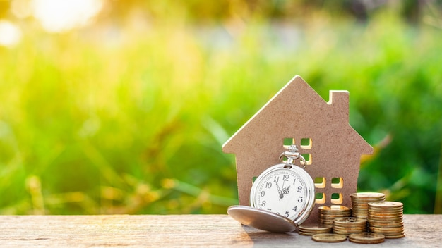Small house model and a clock with golden coins pile Premium Photo
