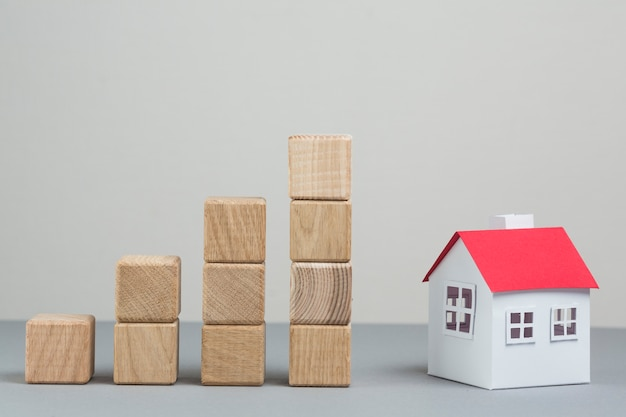 Small house model and stack of increasing wooden block on grey backdrop Free Photo