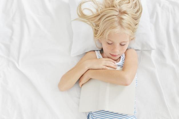 ベッドでおもしろい話を読んだ後、本を手に持って寝て、白い枕と寝具に横になって、楽しい夢を見て眠る美しい容姿の小さな子供。寝る前に読む 無料写真