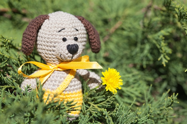 A small knitted brown dog with a yellow ribbon in summer garden. knitted toy, handmade, amigurumi Premium Photo