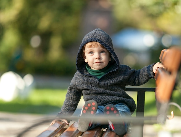Small little boy sitting on a bench Free Photo