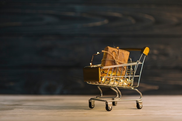Small metallic grocery cart with gift box Free Photo