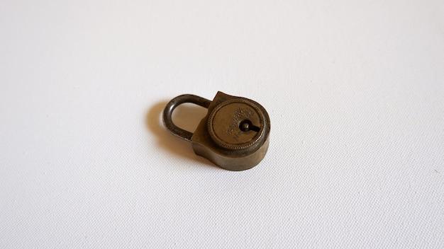 Маленький металлический замок на белой поверхности Бесплатные Фотографии