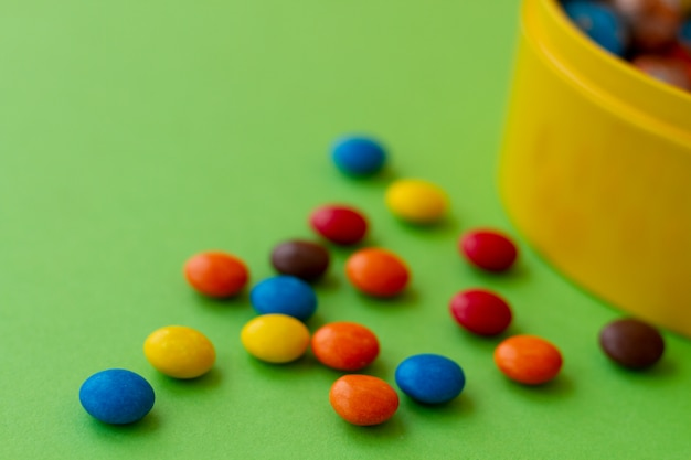 Small multi-colored candies in dragee glazes next to a yellow jar for sweets Premium Photo
