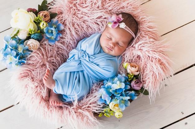 Маленький новорожденный в цветочной корзине Premium Фотографии